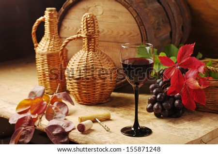 One glass of red wine, two bottles, grapes and oak barrel.  Wooden background. Shallow focus.