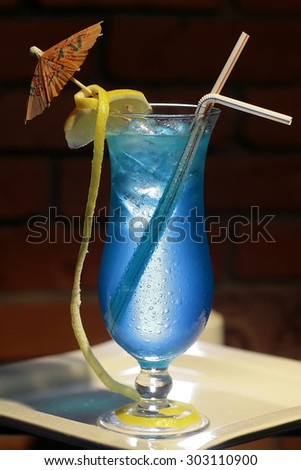 One glass with alcoholic blue lagoon cocktail of liqueur blue curacao vodka sprite yellow lemon citrus fruit and ice cubes with drink straws and umbrella on brick background, vertical photo - stock photo