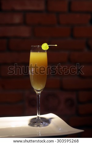 One glass with alcoholic mimosa or valencia cocktail of apricot liqueur orange juice sparkling dry wine and yellow cherry with stem on white plate brick wall background, vertical photo - stock photo
