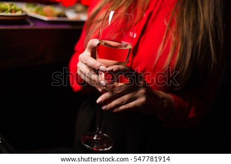 one glass with white  wine, in a hands, in an interior