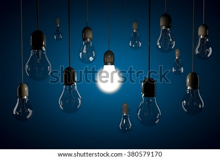 One glowing bulb illuminating dark bulb hanging on wires on blue background - stock photo