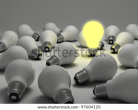 One glowing light bulb amongst the unlit incandescent bulbs on white background - stock photo