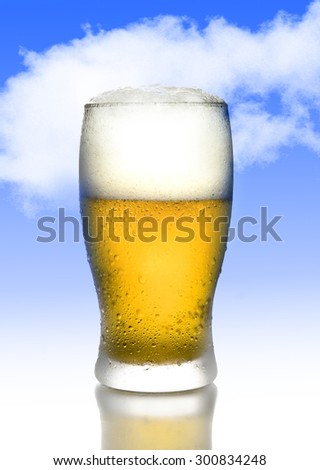 one golden beer with frost and bubbles in full tempting glass with white foam isolated on a blue sky background in alcoholic refreshing drink concept - stock photo