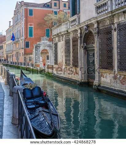 One gondola is waiting for passengers on a picturesque street in Venezia, Italy