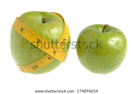 One green apple wrapped with measuring tape and another green apple isolated on white