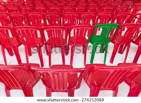 one green chair among many red ones - stock photo