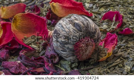 One green chinese jasmin  tea ball.Dry tea.Jasmin pearl on green tea,Hibiscus tea,roses background. herbal tea.Magenta-colored calyces.Jasmine flower wallpaper.Blooming flower tea ball.Nice structure - stock photo