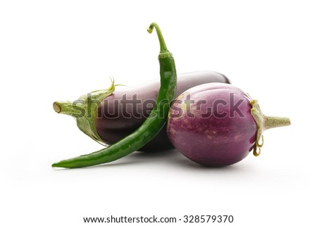 One green hot chilly pepper with two eggplants - stock photo