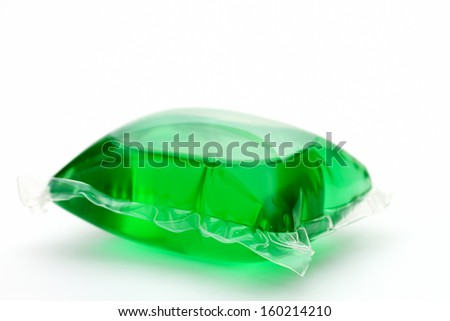 One green laundry detergent capsule on white - stock photo