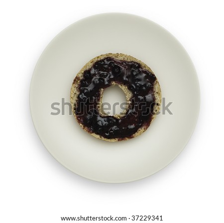 One half of a Whole Grain Bagel with Blueberry Marmalade on a white plate. Isolated on white background. Saved with clipping path.
