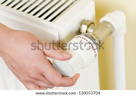 One hand adjust thermostat valve - stock photo