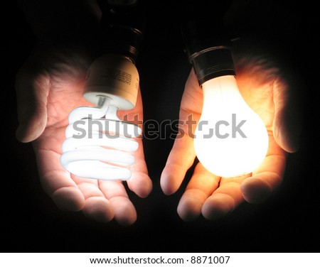 One hand holding a compact fluorescent bulb, the other an incandescent bulb, showing comparison - bulb lit - stock photo