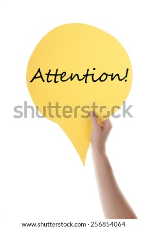 One Hand Holding A Yellow Speech Balloon Or Speech Bubble With English Text Or Word Attention Isolated On White - stock photo