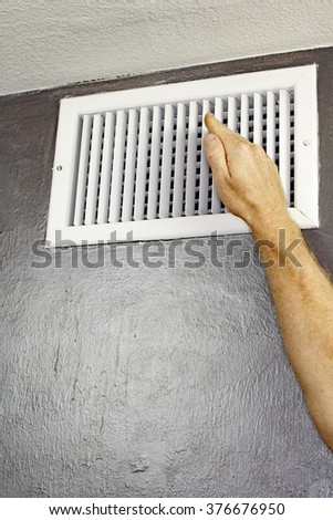 One hand of an adult male raised in front of an upper wall air vent checking for air flow. A man holding a hand up in front of an air vent checking the air temperature.