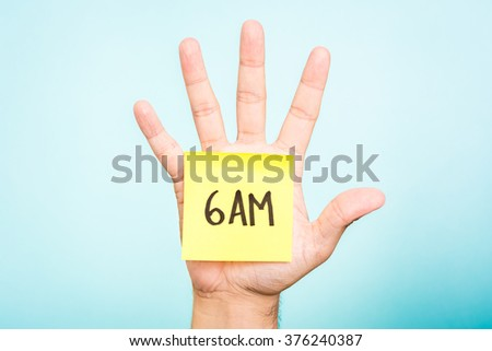 One hand up and open, showing his palm with a yellow paper note illustrated with the text 6AM, all over blue background. It  is useful for time managemente concept.