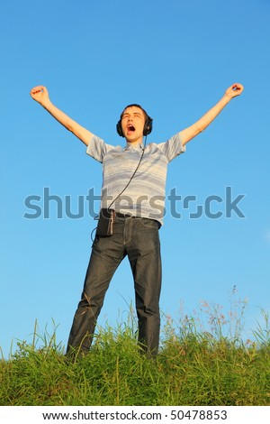 one handsome man is standing on a meadow with raised hands. headphones on his hand.