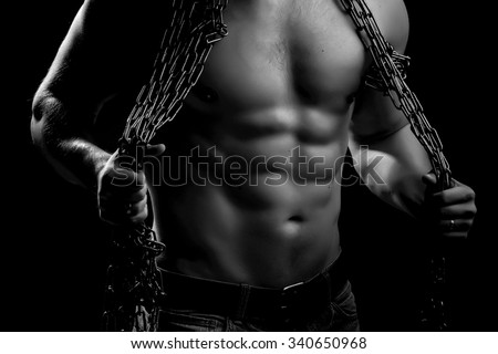 One handsome sexual strong young man with muscular body in blue jeans holding rope with hands hanging on neck and shoulders standing posing in studio black and white, horizontal picture - stock photo
