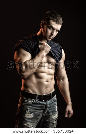 One handsome sexual strong young man with muscular body in blue jeans with shirt on shoulder standing posing in studio on black background, vertical picture - stock photo