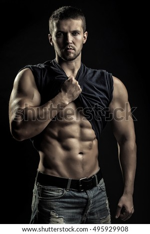 One handsome sexual strong young man with muscular body in blue jeans with shirt on shoulder standing posing in studio on black background, vertical picture