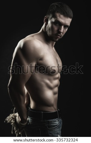 One handsome sexual strong young man with muscular body in blue jeans with tied hands by rope standing in studio on black background, vertical picture - stock photo
