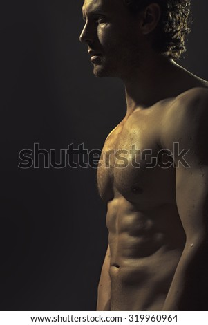 One handsome strong young naked sweat muscular male model with curly hair and beautiful straight body standing in studio on black background, vertical picture - stock photo