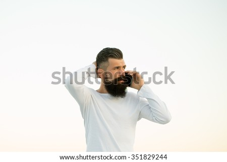 One handsome young bearded pensive business man in white sweater holding and speaking on cell phone outdoor on light sky natural background, horizontal picture - stock photo