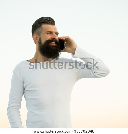 One handsome young bearded smiling business man in white sweater holding and speaking on cell phone outdoor on light sky natural background, square picture - stock photo