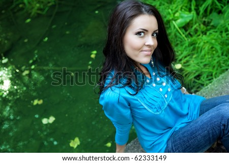 One happy beautiful young brunette woman outdoors - stock photo