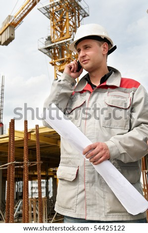 One happy engineer builder with blueprint at construction site speaking on mobile phone - stock photo