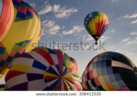 One hot-air balloon ascending above other inflating balloons at a festival. (Readington Balloon Festival) - stock photo