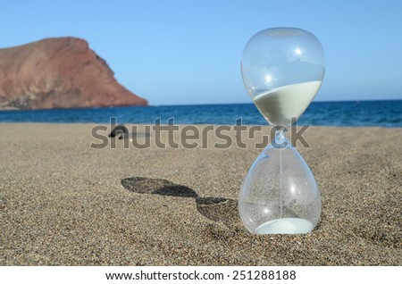 One Hourglass on the Sand Beach Near the Ocean Time Concept - stock photo