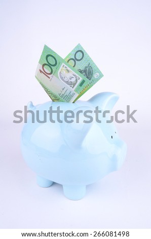 One hundred Australian dollar note inserted into a blue piggy bank - stock photo