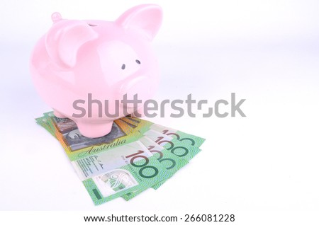 One hundred Australian dollar notes and a pink piggy bank - stock photo