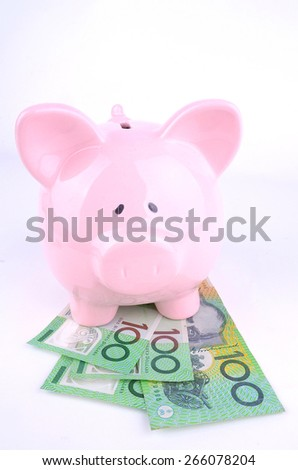 one hundred Australian dollar notes under a pink piggy bank shot in the studio - stock photo