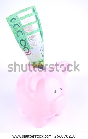 One hundred Australian dollars in a pink piggy bank shot in the studio - stock photo
