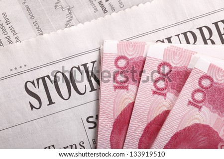 One hundred Chinese bank notes on stock section of a newspaper - stock photo