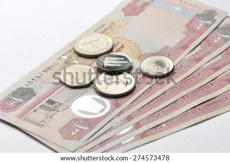 One hundred Dirham currency notes and coins on white background. - stock photo