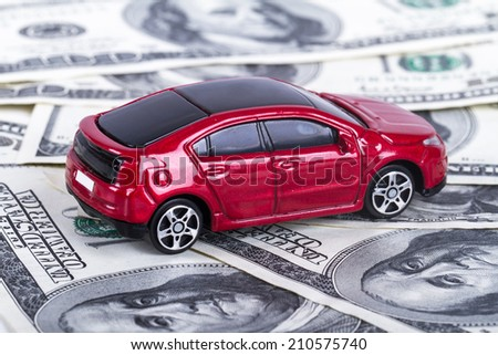 One hundred dollar banknotes with small, toy car. - stock photo