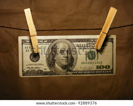 One hundred dollar bill hanging on a clothes pins - stock photo