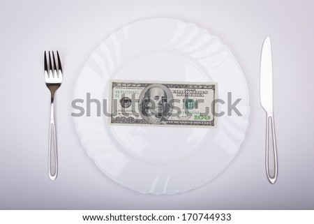 One hundred dollar bill lies on white plate with knife and fork on opposite sides