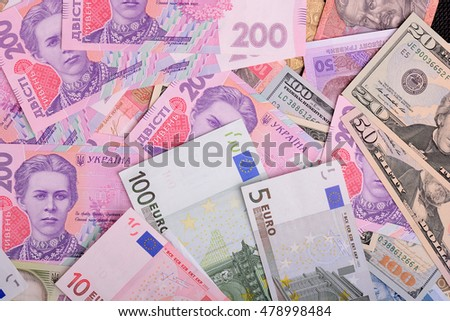 One hundred dollar bill on the background of ukrainian hryvnia and european euro