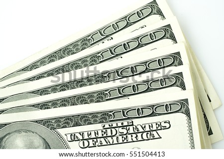 One hundred dollar bills against white abstract background.