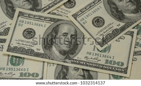 One hundred dollar bills chaotically lying on the table close up. The motion camera slider. Portrait of Benjamin Franklin - 3