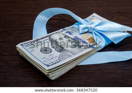 one hundred dollar bills in blue gift ribbon