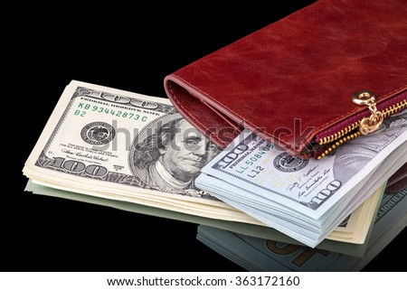 One hundred dollar bills on a leather purse isolated on a black background