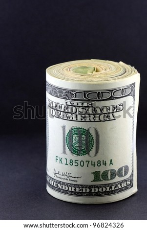 One Hundred Dollar Bills Rolled Up. - stock photo