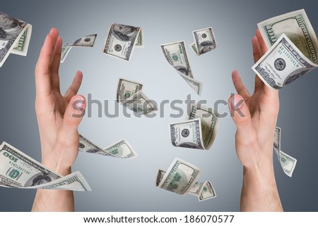 One hundred dollar money banknotes flying and falling on young male hands.