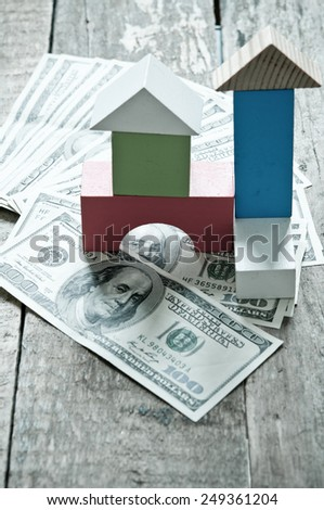 One hundred dollars and house from wooden building blocks - stock photo