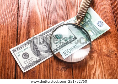 One hundred dollars and one hundred euros banknotes with vintage magnifying glass on them lying on wooden table