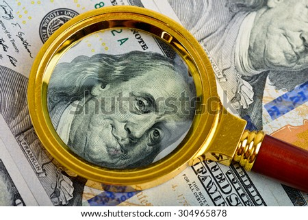 One hundred dollars banknotes with vintage magnifying glass - stock photo